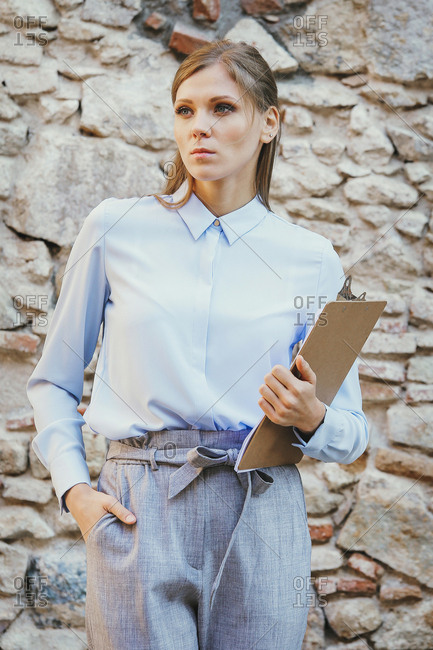 Serious businesswoman holding clipboard