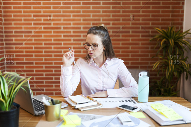 Businesswoman taking notes on table in office