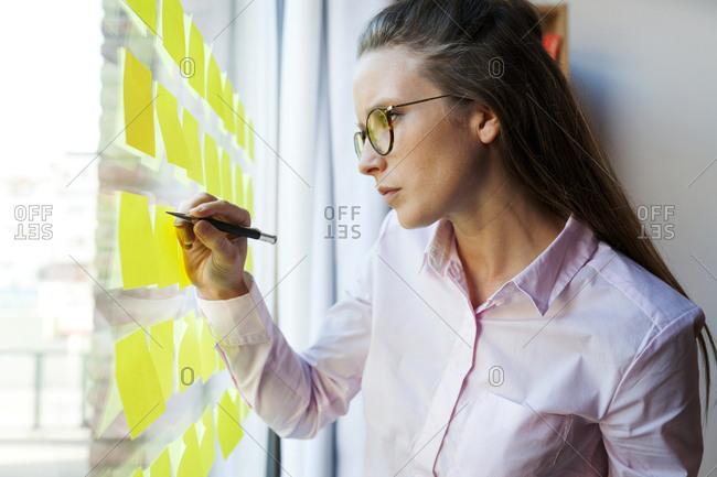 Businesswoman writing on post it at glass pane
