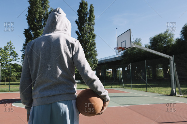 Man holding basketball- hoop in the background