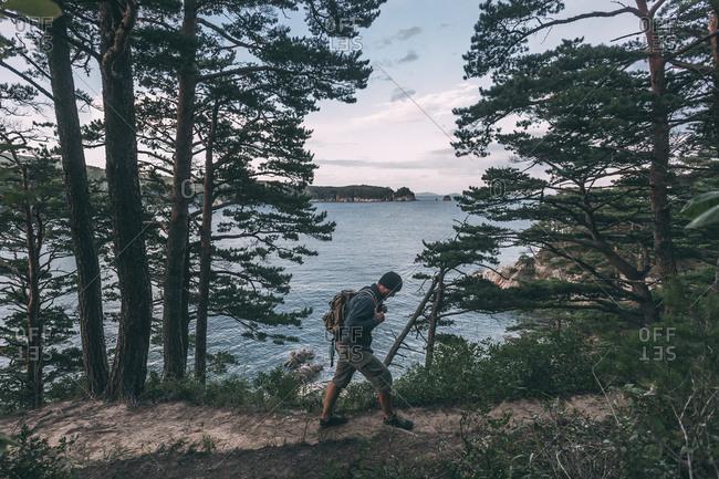 Russia- Far East- Khasanskiy- Japanese sea- man hiking at Telyakovsky bay