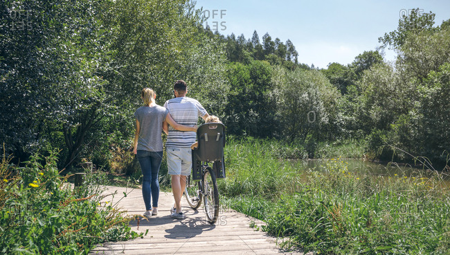 Family with bicycle walking on wooden walkway