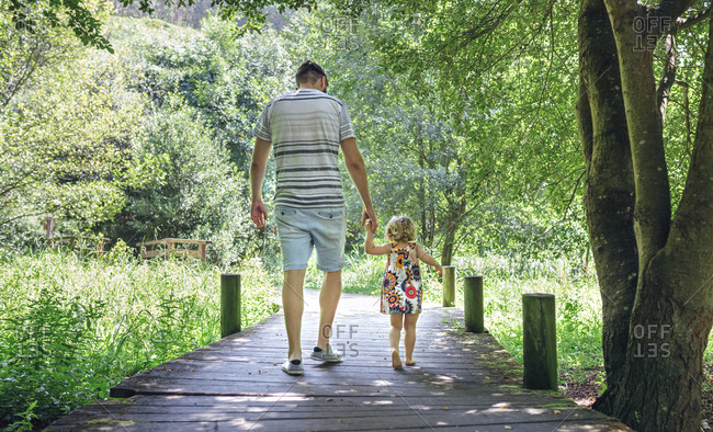 Father walking with his little daughter on a wooden walkway in the countryside