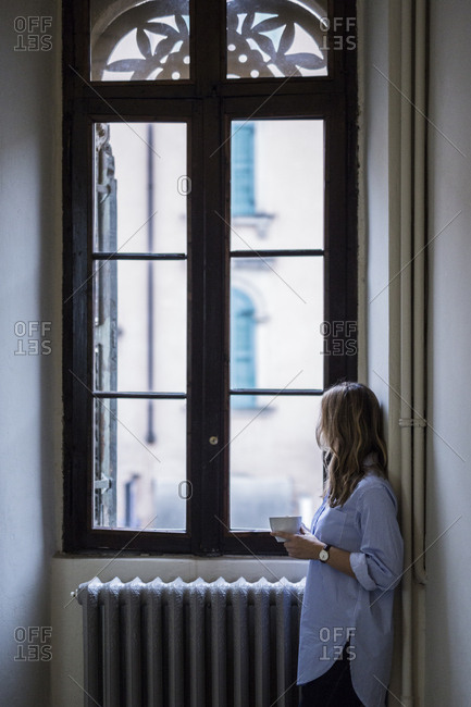 Woman with cup of coffee at home looking out of window