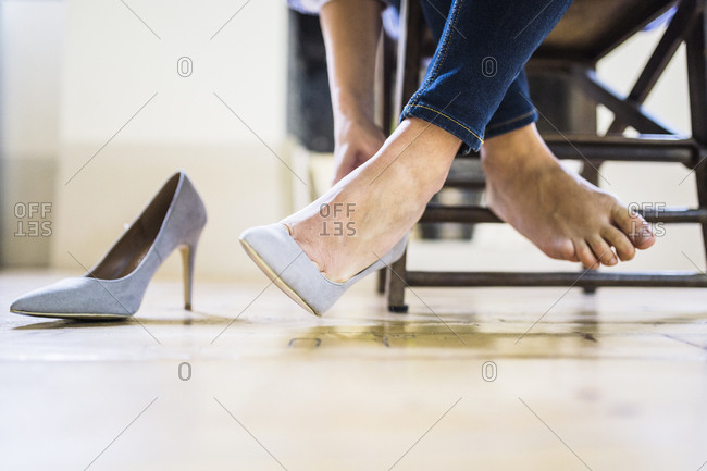 Businesswoman sitting taking off her high heels