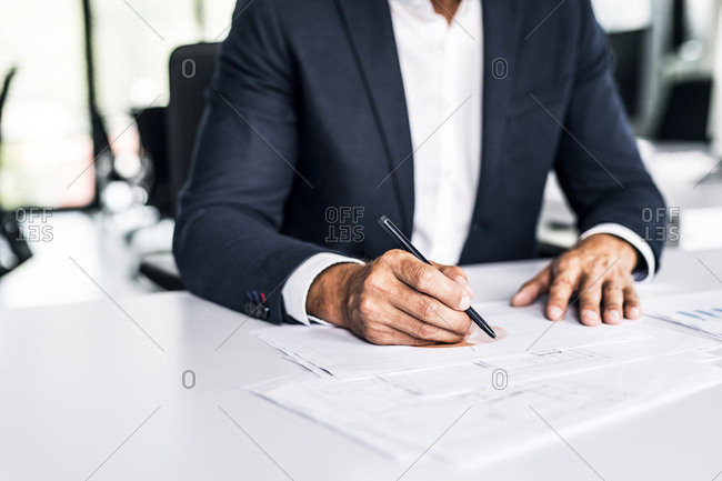 Close-up of businessman with documents at desk in office