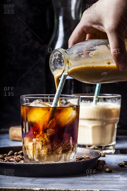 Hand pouring homemade vanilla flavored coffee creamer into a glass with iced coffee