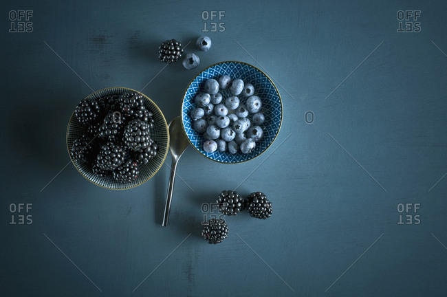 Bowl of blueberries and bowl of blackberries on blue ground