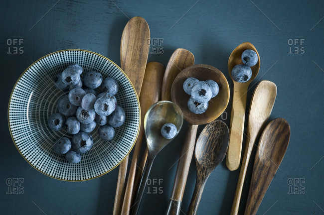 Bowl of blueberries and different spoons on blue ground