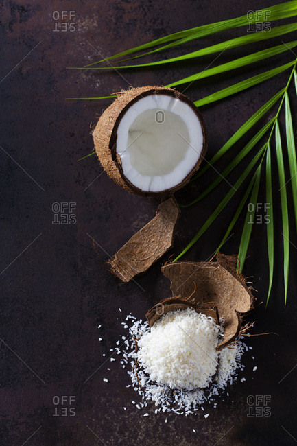Opened coconut- coconut husk and pile of coconut flakes
