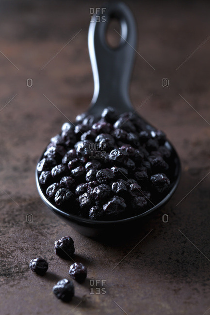Spoon of dried chokeberries on rusty metal