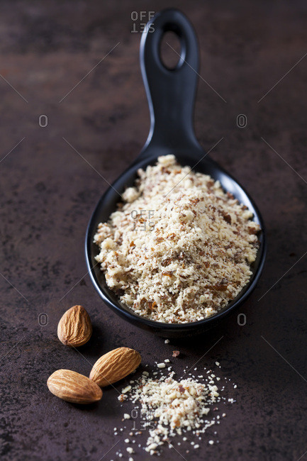 Spoon of almond flour and almonds on rusty ground