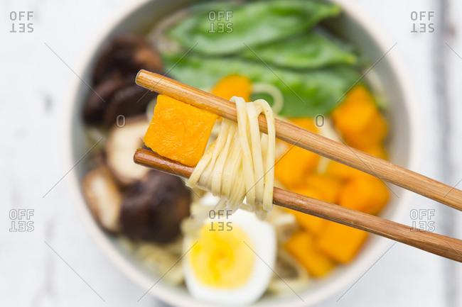 Ramen with noodles- egg- hokkaido pumpkin- shitake mushroom in bowl- chopsticks with noodles