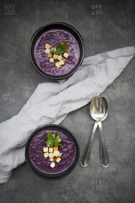 Bowl of red cabbage soup garnished with croutons