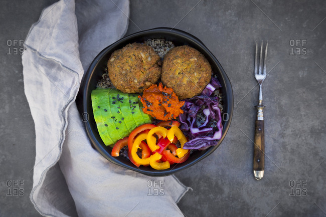 Lunch bowl of quinoa- red cabbage- bell pepper- avocado- quinoa fritters- ajvar and black sesame