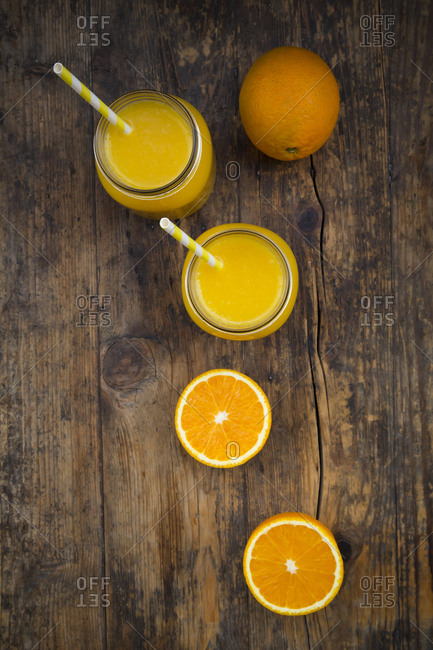 Freshly squeezed orange juice in jars with straws