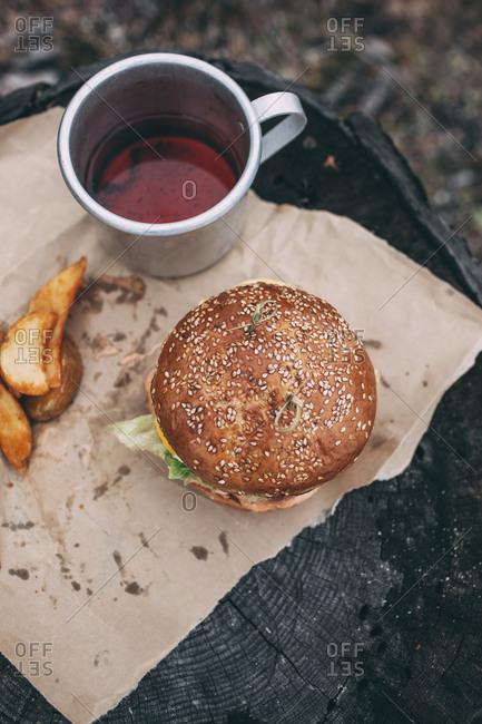Burger and mug with tea on stamp