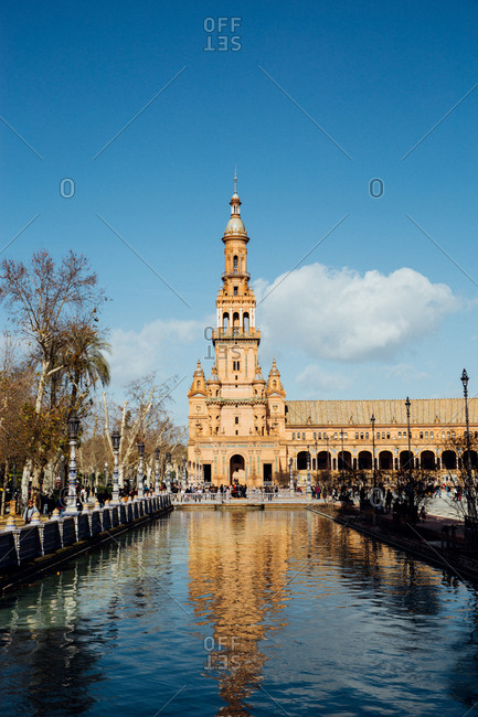 Seville, Spain - January 10, 2018: The South Tower of Plaza de Espana reflected in the canal