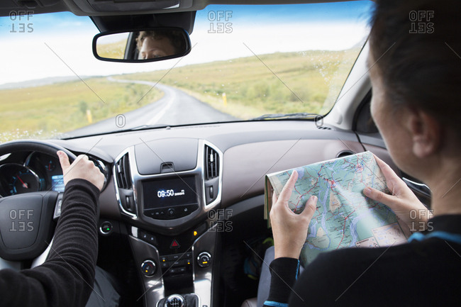 The interior of a car with a woman reading a map
