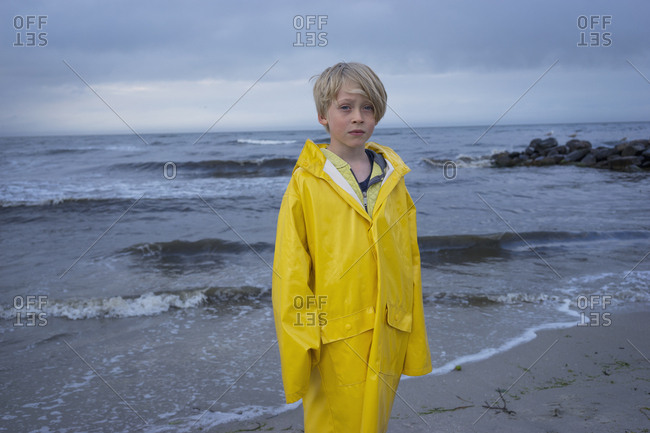 A young boy at the beach in wet weather gear