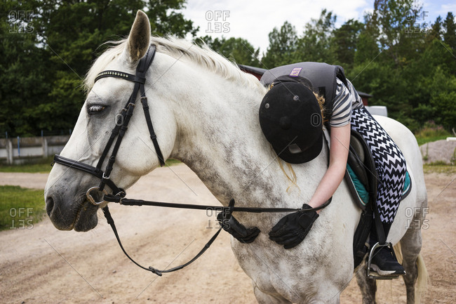 Smaland, Sweden - July 17, 2016: A young girl hugging her horse