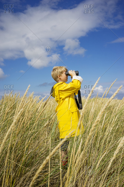 A young boy in wet weather gear looking through binoculars
