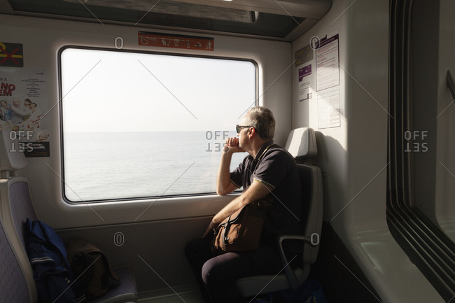 Catalonia, Spain - October 27, 2016: A man travelling on a train looking out the window