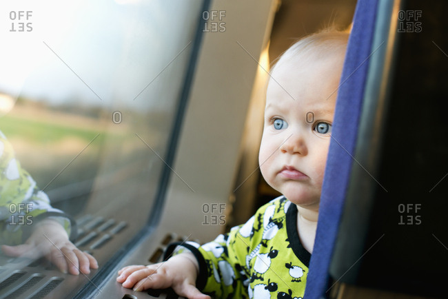A baby looking out the window of a train