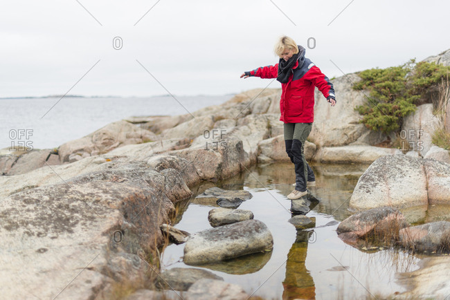 Woman by rock pool in Norrpada, Sweden