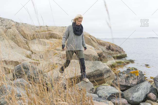 Woman on rocks by sea in Norrpada, Sweden