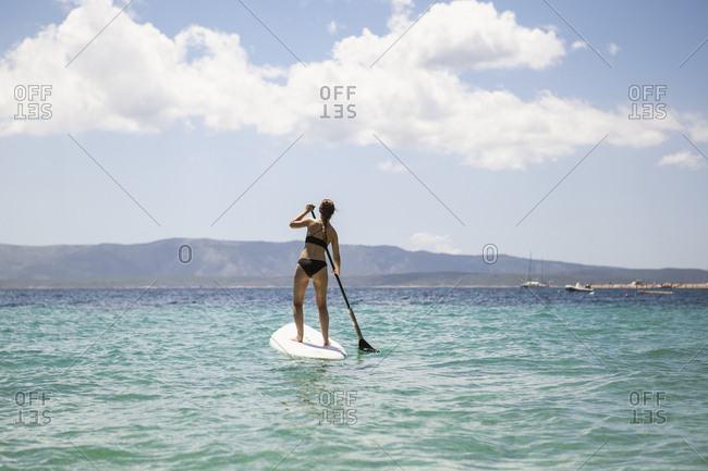 A woman paddle boarding in Croatia