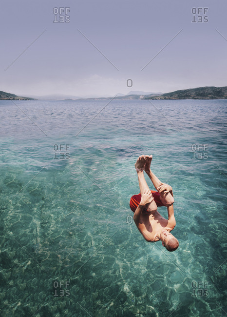 A young man somersaulting into the sea