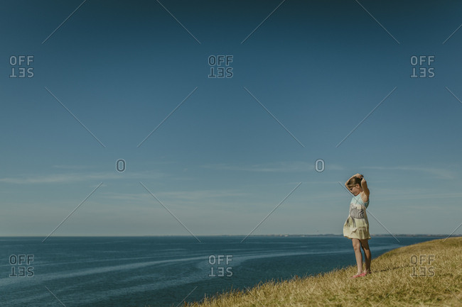 Skane, Sweden - August 6, 2015: A young girl looking out to sea