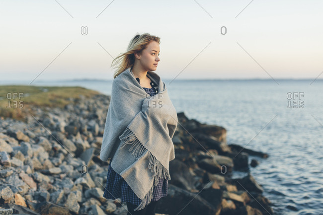 A young woman wrapped in a shawl looking out to sea