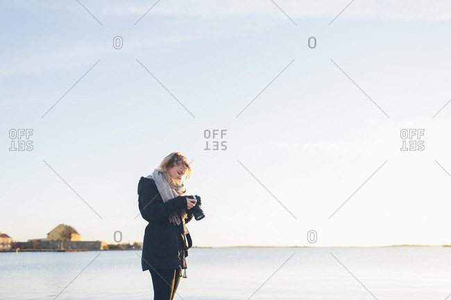Woman holding a camera by the sea