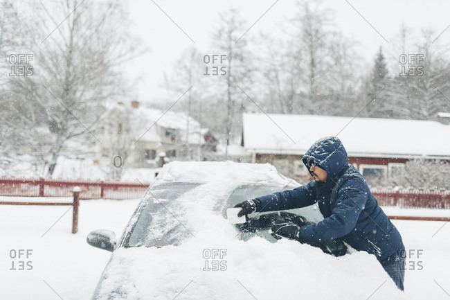 Man clearing snow from his car