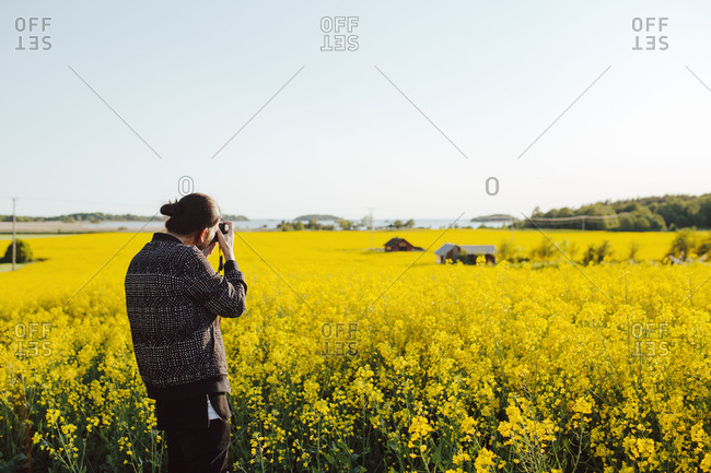 A young man taking a photograph of a country scene