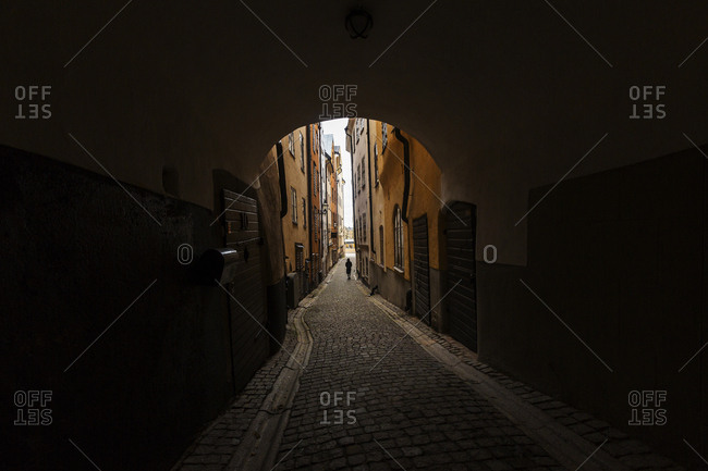 Stockholm, Sweden - November 3, 2016: Person walking through cobblestone tunnel