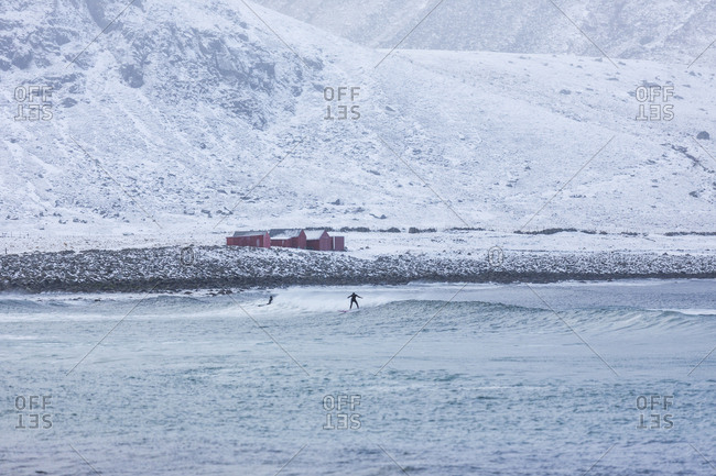 People surfing in the sea below snowy hills in Norway