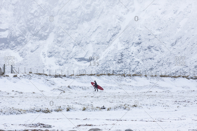 A person carrying a surf board across snowy ground in Norway
