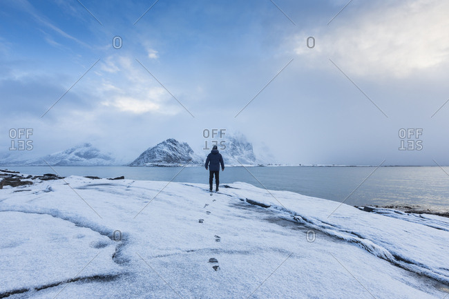 A man standing in snow looking out to sea