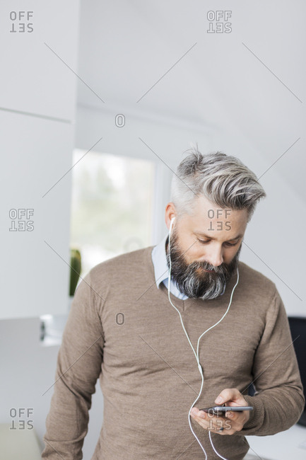 A man with ear phones in listening to his cell phone