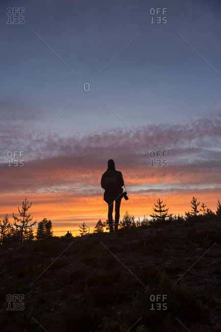 Silhouette of a woman with a camera at sunset in Vasterbotten, Sweden