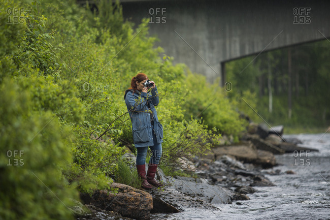 Woman taking photographs by river
