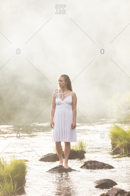 Woman wearing a white dress standing in river