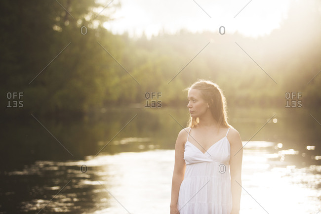 Woman wearing white dress by river