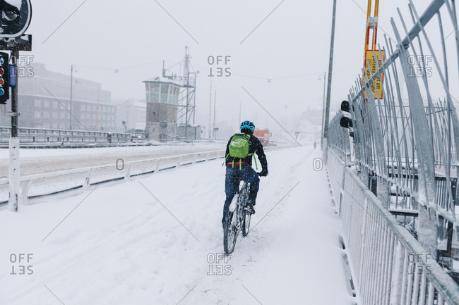 Man cycling in snow in Stockholm