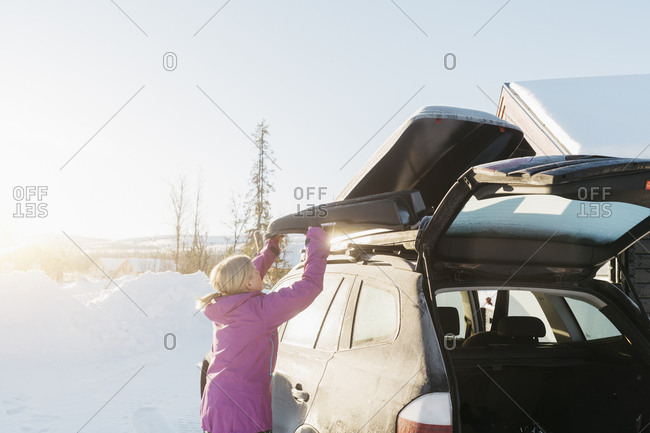 Woman lifting a sled from a car during winter