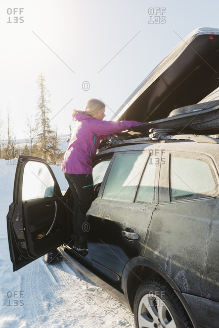 Woman unpacking a car during winter