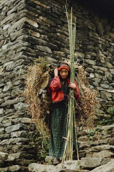 Langtang, Nepal - November 4, 2011: Tamang girl holding a bunch of bamboo shoots and carrying a load on her back